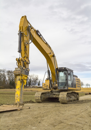 yellow excavator at a loamy construction site Imagens