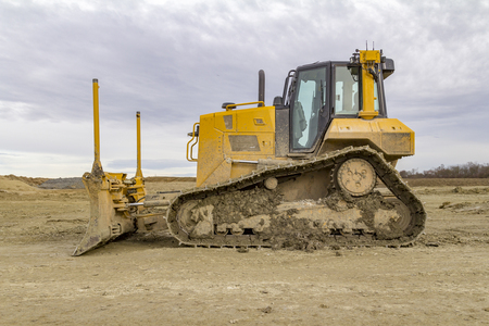 yellow bulldozer at a loamy construction site