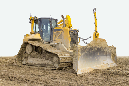 yellow bulldozer at a loamy construction site, partly isolated in white back