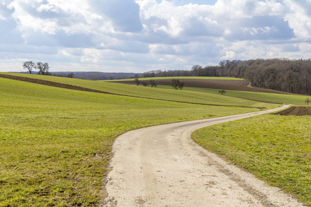 idyllic and rural panoramic scenery with fields and meadows including a field path in Hohenlohe, a area in Southern Germany at early spring time time Stock Photo