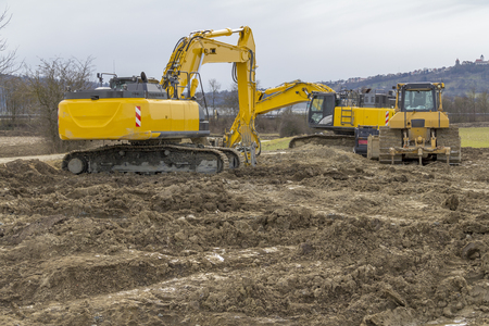 two yellow excavators at a loamy construction site Stock Photo