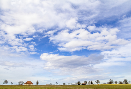 lots of partly clouded sky and little rural landscape at early spring time in Southern Germany Banco de Imagens - 102833523