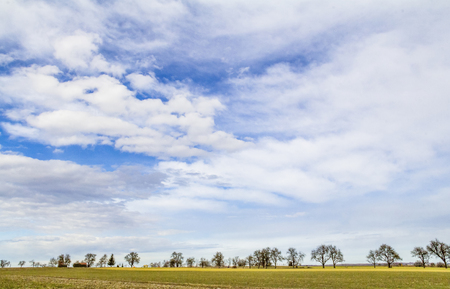 lots of partly clouded sky and little rural landscape at early spring time in Southern Germany Stock Photo