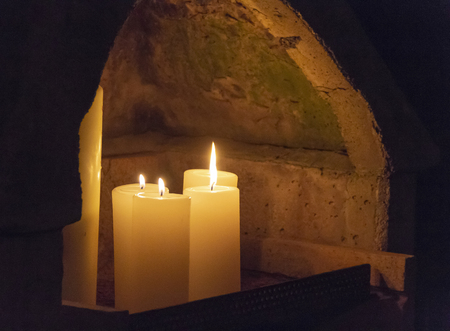 Night scenery showing a niche in a wall with burning candles 스톡 콘텐츠