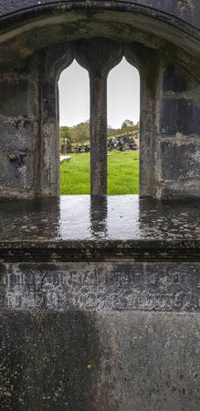Old graveyard seen through a historic chapel window in Ireland Standard-Bild - 115382116