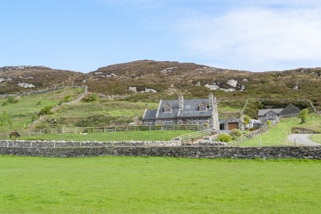 Traditional house and surrounding stone walls seen in western Ireland Standard-Bild - 115381911