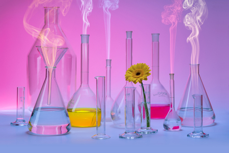 Variety of partly filled laboratory glassware including a flower head and some smoke in colorful ambiance Standard-Bild - 115381919
