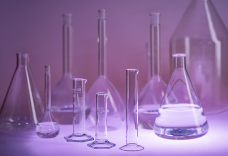 Variety of partly filled laboratory glassware in violet ambiance
