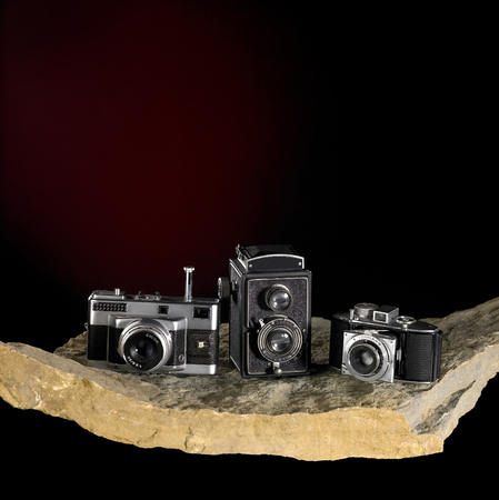 Nostalgic cameras on stone surface in dark back