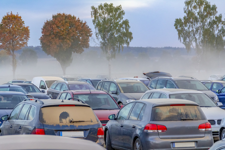 dusty parking space scenery on a field including lots of dust covered cars at evening time in Southern Germany Banco de Imagens
