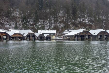 Scenery with lots of boathouses around Schoenau am Koenigssee in Bavaria at winter time