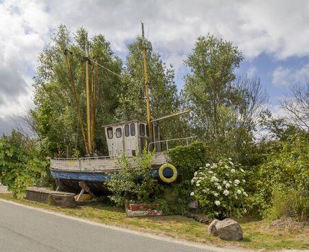 roadside scenery showing a rundown fishing cutter seen at Varel in East Frisia, Germany