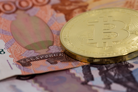 rubles: gold bitcoin with bills rubles Stock Photo