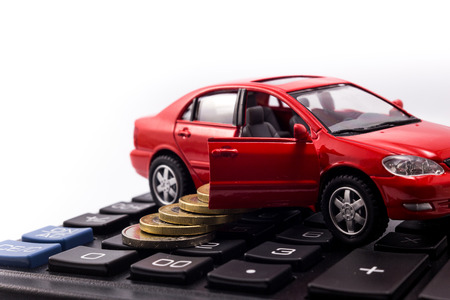 car model and coins on calculator