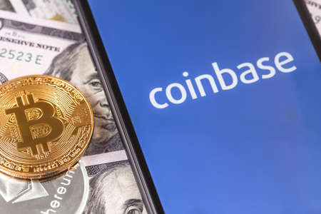 dollars, bitcoin, ethereum and smartphone with Coinbase logo on the screen. Coinbase is a digital currency exchange. Moscow, Russia - February 13, 2019 Editorial