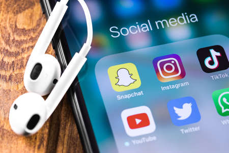 Social media apps. Instagram, Snapchat, Twitter, Youtube icons mobile apps on the screen Apple iPhone with Earpods. Moscow, Russia - March 12, 2019