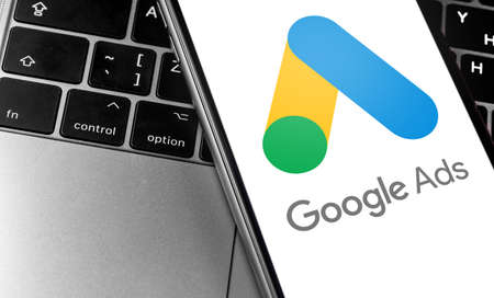 closeup keyboard laptop and Google AdWords app icon on smartphone screen. Google is the biggest Internet search engine in the world. Moscow, Russia - April 27, 2019