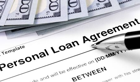 personal loan agreement application form with pen and money, dollars