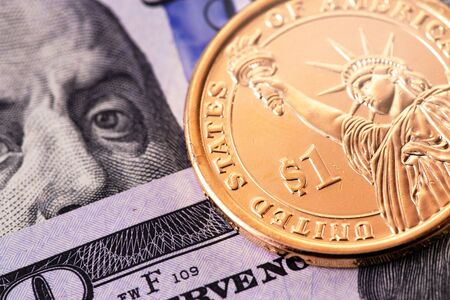 one dollar golden coin and hundred dollars banknotes, macro