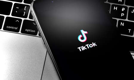 iPhone with TikTok logo on the screen. TikTok is app to create and share videos. Moscow, Russia - April 27, 2019