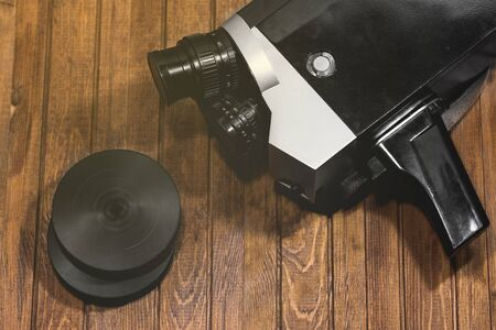 Retro cinematography film camera on wooden boards background