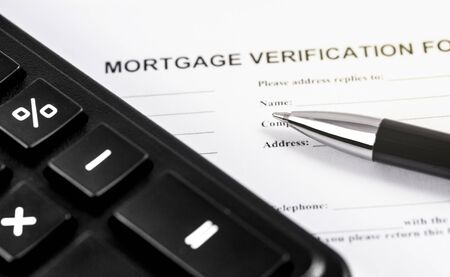 mortgage verification form application with black pen and calculator closeup