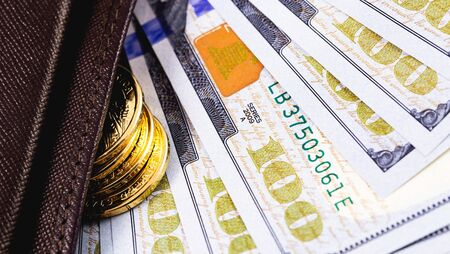 stack golden metal coins and dollars banknotes in wallet closeup