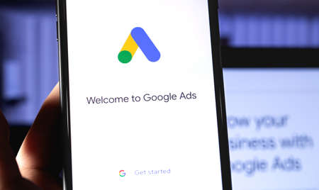 Google Ads mobile app on the screen smartphone with notebook background closeup. Ads is a service of contextual, basically, search advertising from Google. Moscow, Russia - October 21, 2019