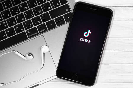 TikTok logo on the display iPhone, notebook and headphones Apple Earpods closeup. TikTok is app to create and share videos. Moscow, Russia - December 23, 2019