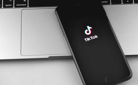 TikTok logo on the screen iPhone, notebook closeup. TikTok is app to create and share videos. Moscow, Russia - December 19, 2019