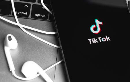 TikTok logo on the sceen iPhone and Apple Earpods headphones closeup. TikTok is app to create and share videos. Moscow, Russia - November 28, 2020