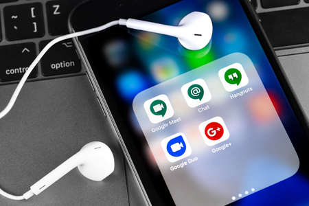 Google Duo, Meet, Chat, Hangouts and Google Plus apps on the screen smartphone with Earpods headphones closeup. Google is the biggest Internet search engine in the world. Moscow, Russia - March 25, 2020 Editorial