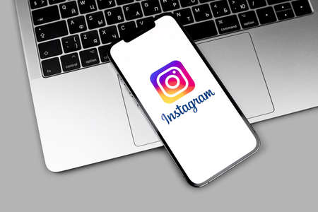 Instagram logo app on the screen iPhone with MacBook closeup. Instagram is a photo-sharing app for smartphones. Moscow, Russia - December 5, 2020