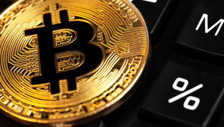 bitcoin cryptocurrency symbol and calculator with percent button, macro Stock Photo