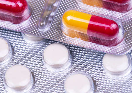 medical pills and capsules, antiviral drugs, blister packaging closeup, macro