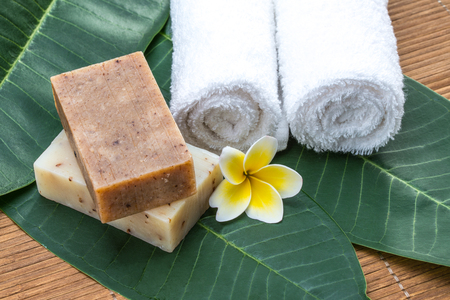 relaxation background: soap, towel, flower, on green leaves for health spa material