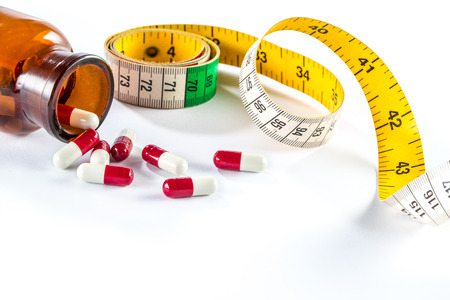 unhealthy diet: Measuring tape with capsule,  Dieting by medicine lose weight Stock Photo