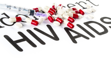 Capsule and Syringe on paper write AIDS and HIV, medication sickness Stock Photo