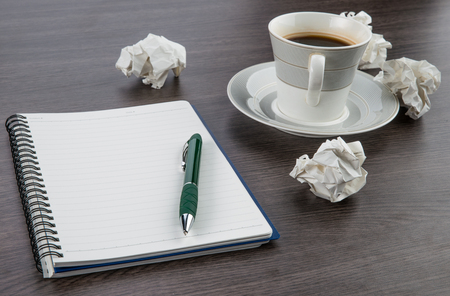 crumple: crumple paper, notebook and pen with cup of coffee on the desk Stock Photo