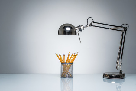 pencil holder: lighting up orange pencil holder stationery with desk lamp on round studio lighting