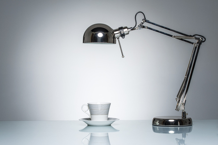 white light: lighting up white mug coffee cup with desk lamp on round studio lighting