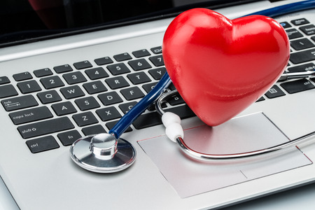 the cardiologist: Cardiologist, heart disease research, stethoscope and heart shape on laptop keyboard Stock Photo