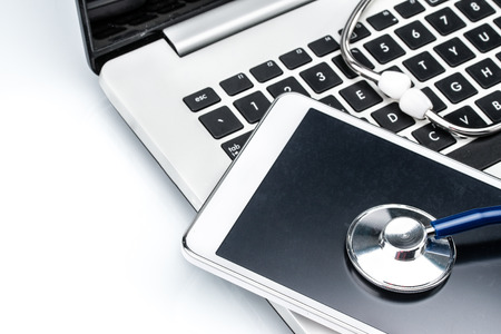 Network Security, stethoscope and Digital Tablet on laptop keyboard, Antivirus Software Stock Photo