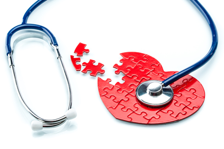 Heart disease, puzzle heart with stethoscope on white background