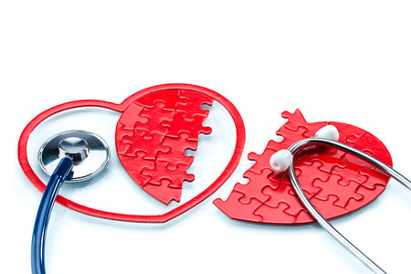 murmur: Heart disease, Split heart-shaped puzzle with stethoscope on white background Stock Photo