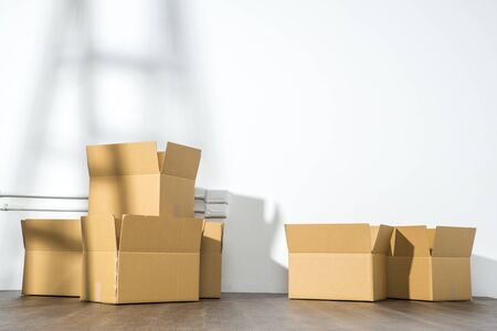 property ladder: Pile of cardboard boxes on white background with  Ladder shadow
