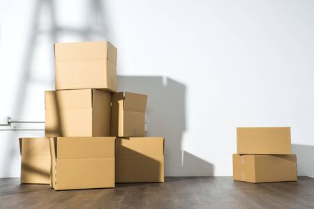 Pile of cardboard boxes on white background with  Ladder