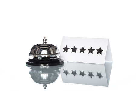 accommodation space: Service bell and 5 stars on the Check in desk with white background Stock Photo