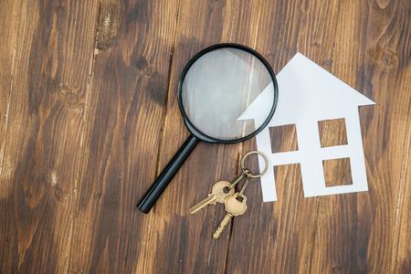 papier huis en sleutel met Vergrootglas, Huizenjacht op houten achtergrond Stockfoto