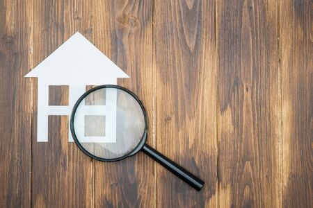 housing search: paper house with Magnifying Glass, House hunting on wooden background